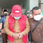 Camat Duduksampeyan, Gresik menutupi wajah dengan topi dari jepretan para wartawan di kantor kejaksaan negeri Gresik pada Senin, 15 Februari 2021