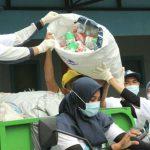 Ning Nurul membantu menaikkan sampah plastik dalam memeriahkan HPSN yang digelar DLH Gresik dan Asbag di Desa Ngargosari, Kecamatan Kebomas pada Sabtu, 20 Februari 2021 ( foto : chusnul cahyadi/1minute.id)
